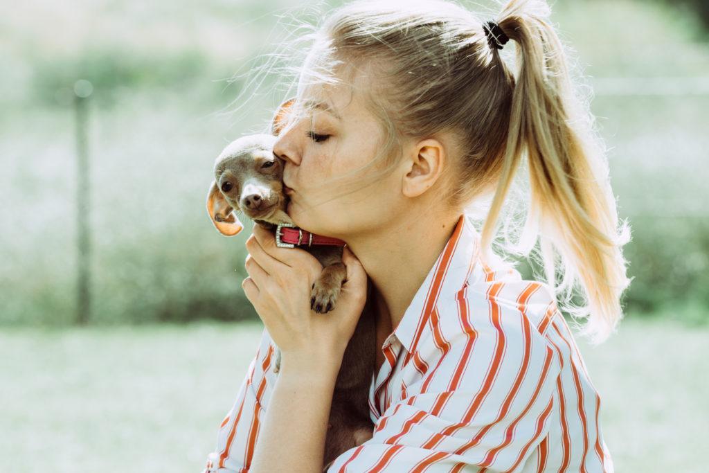 Eine Frau küsst ihren Hundewelpen